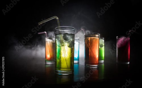 Poster Bar collection of colorful shots with lemon on bar; set of alcohol mini cocktail shooters with lime;