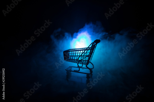 Fotografia Empty shopping trolley on dark toned foggy background with some copy space