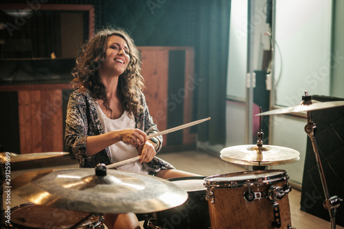 Woman playing drums during music band rehearsal - 291259699