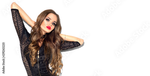 obraz dibond Party girl portrait. Halloween Witch with bright make-up and long hair. Smoky eyes. Beautiful young woman posing in sexy black leather dress. Isolated on white background
