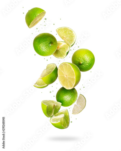 Whole and sliced fresh lime in the air, isolated on a white background