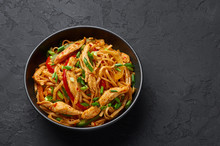 Chicken Schezwan Noodles Or Hakka Or Chow Mein In Black Bowl At Dark Background. Schezwan Noodles Is Indo-chinese Cuisine Hot Dish With Udon Noodles, Vegetables And Chilli Sauce. Copy Space