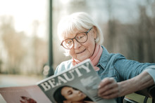 Grey-haired Beaming Lady In Years Reading A Fashion Magazine