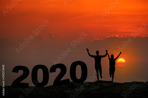 Silhouette young couple in love enjoy good time together during sunset and 2020 new year text on top Mountain, sky and sunset background Wallpaper Mural