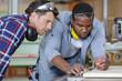 Leinwanddruck Bild - two carpenters working together in workshop