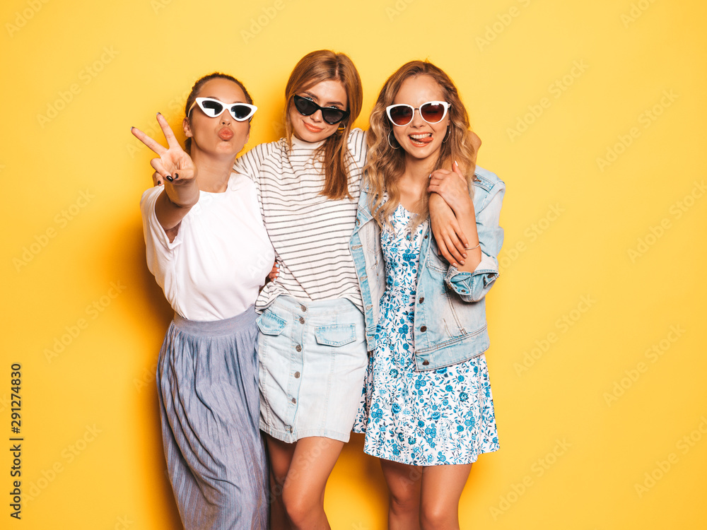 Fototapeta Three young beautiful smiling hipster girls in trendy summer clothes. Sexy carefree women posing near yellow wall in studio. Positive models going crazy and having fun in sunglasses