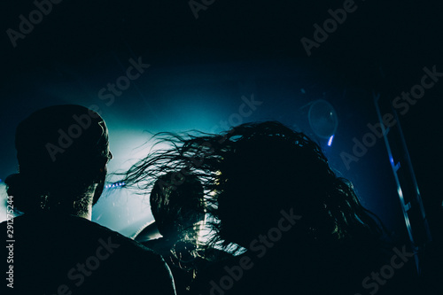 A long-haired man headbanging during the show. Strands of hair in deep blue and yellow stage lights. - 291275244