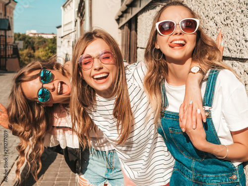 Portrait of three young beautiful smiling hipster girls in trendy summer clothes Tablou Canvas
