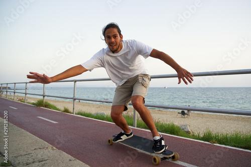 Joven con look moderno patinando en su longboard mientras se dispone a chocar la Fototapet
