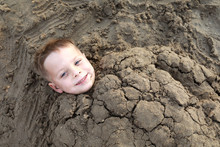 Smiling Kid Buried In Sand On Beach
