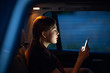 Young woman profile portrait lit sitting in back seat of car vehicle with mobile phone. Taxi concept.