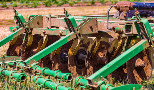 Photo An Old Tractor Plow Laying in a Field