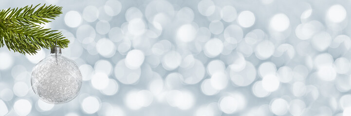 Silver christmas ball hanging from a christmas tree branch on panoramic holiday lights background with copy space