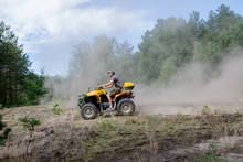 Man Riding A Yellow Quad ATV A...