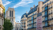 canvas print picture Paris, charming street and buildings, typical parisian facades in the Marais, with Notre-Dame cathedral in background