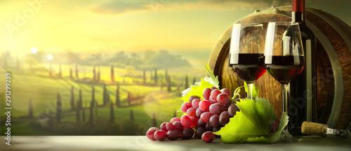 autumn countryside wine background; vine, red wine bottles, wineglass, wine barrel; wine tasting concept - 291299239