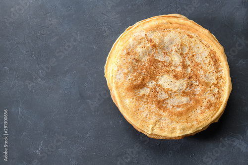 Stack of pancakes on dark rustic background, top view with free text space