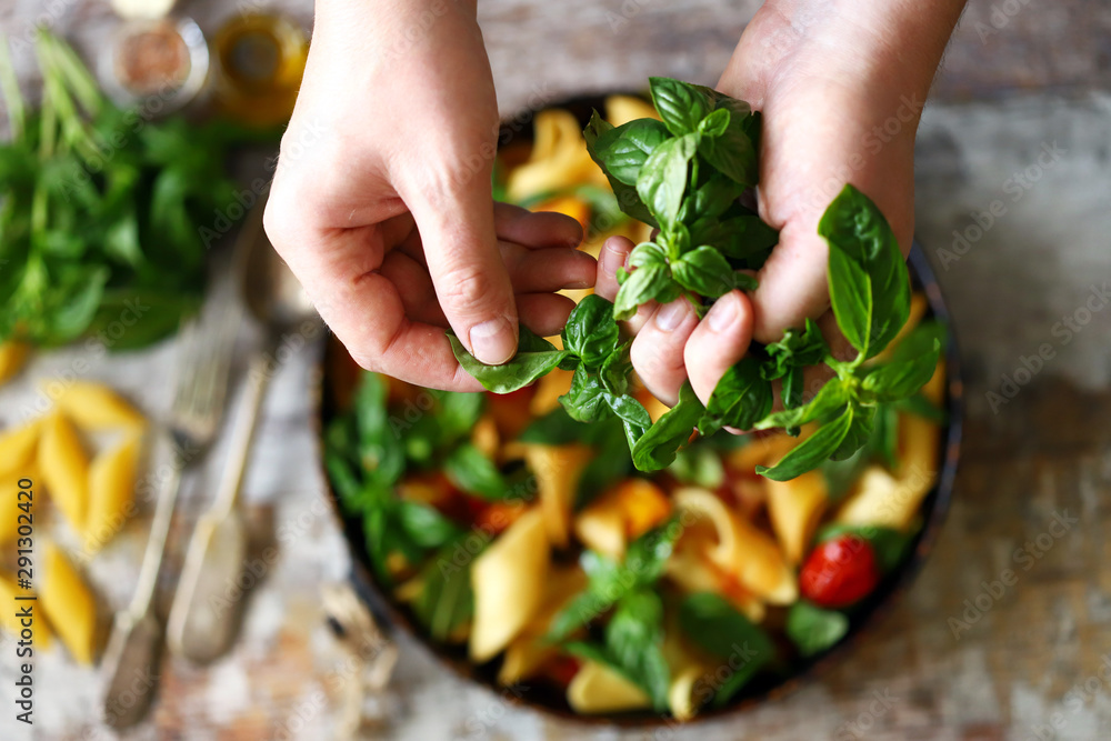 Fototapety, obrazy: Hands of a chef with basil for cooking Italian pasta. Cooking one pan pasta.