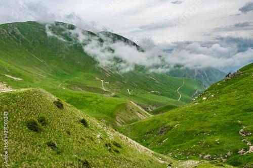 Fototapeta Green mountain landscape with dirt road traversing hillsides obraz na płótnie