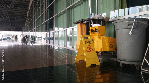 Fotografija The warning signs cleaning and caution wet floor in the building and janitorial car