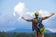Male tourists with backpack standing outdoors with arms spread,Man enjoying with the top of the mountain.concept of travel and freedom