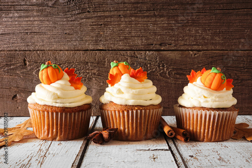 Fall pumpkin spice cupcakes with creamy frosting and autumn toppings. Row against a rustic wood background.