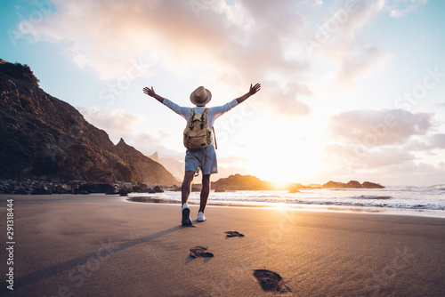 Fototapeta Young man arms outstretched by the sea at sunrise enjoying freedom and life, people travel wellbeing concept obraz