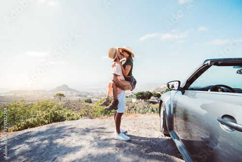 Couple in love kissing on a cliff at road trip with a convertible car Obraz na płótnie
