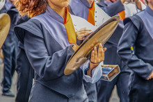 Girl In High School Marching Band Playing The Cymbals With Determined Looking Chin - Unrecognizable Band Members And Motion Blur On Hands