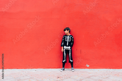 Fényképezés  Boy in skeleton costume standing in street on the red background
