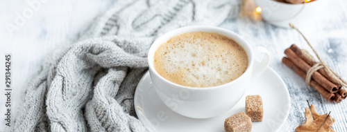 Cup of coffee, brown sugar, knitted scarf, garland. Autumn mood. Cozy autumn composition. Hygge concept. Soft focus - 291344245