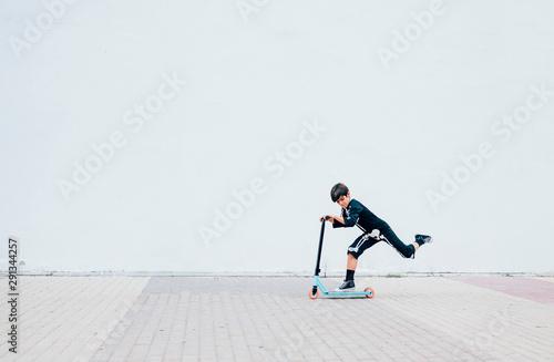 Obraz na plátně  Boy in skeleton costume standing in street with scooter