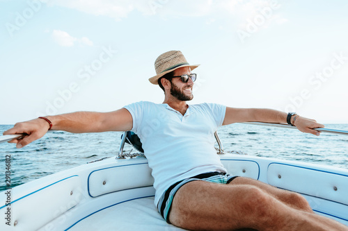 Young man enjoying a view of the sea from the boat