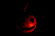 Pumpkin Head Peers Out Of The Darkness Backlit By Fire