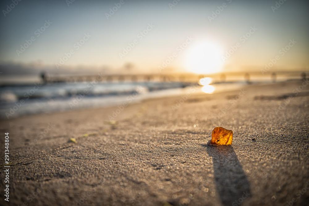 Fototapety, obrazy: Bernstein im Sonnenaufgang am Strand