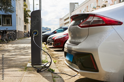 Fotografia Cropped shot of silver electric car at charging station with power cable supply plugged in against cityscape background