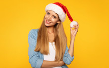 Young And Beautiful. Attractive Woman In A Blue Shirt With Long Fair Hair Smiles And Looks At The Camera Holding A Pompom Of Her Christmas Hat In Left Hand While Posing Over Yellow Isolated Background