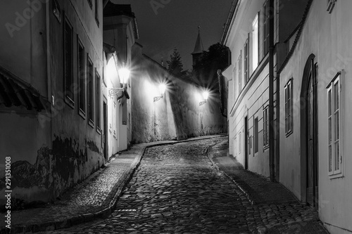 Hidden fairytale street in Prague Czech Republic Novy Svet quarter enlightened by street lamps during night black and white