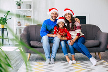 A Joy To Be Together. Mother, Father And Their Little Brunette Daughter Pose In Blue Reindeer Sweaters And Red Santa Hats Sitting On The Grey Couch While Hugging And Smiling