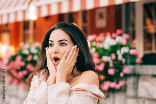 Fotografia  Close up portrait of beautiful young woman with long shiny hair, surprised facia