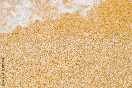Fotografija  Background and texture of coarse sea sand with a wave, running from top left out of focus