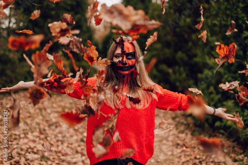 Photo sur Toile Oiseaux sur arbre Young blonde girl with halloween face art posing outdoor. Helloween celebration concept.