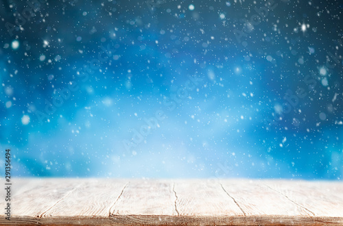 fototapeta na lodówkę Beautiful winter background with wooden old desk and blurred blue sky. Winter, New Year and Christmas concept with snowy background.