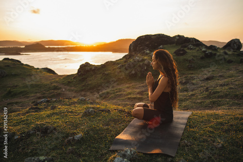 Fototapeta Woman doing yoga alone at sunrise with mountain and ocean view