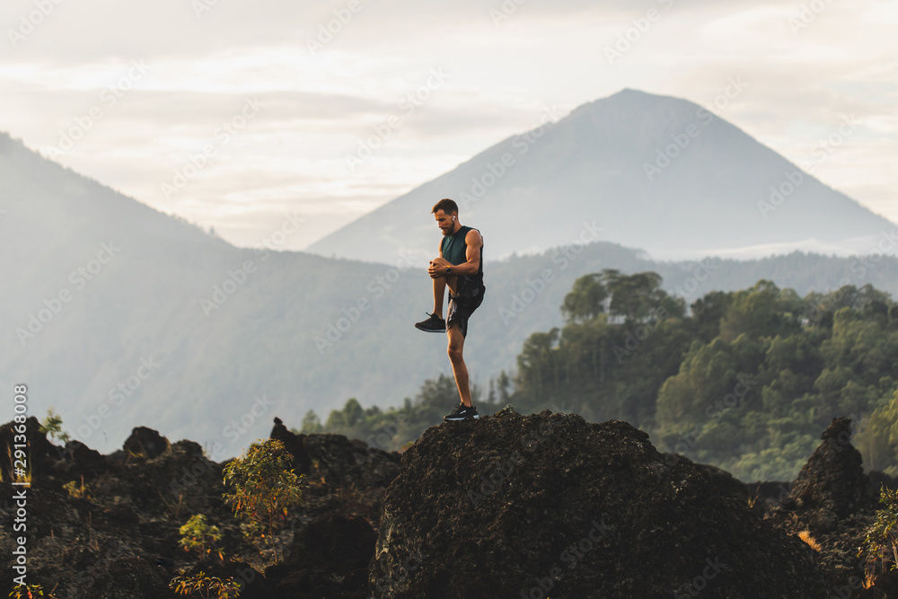 Obraz Man doing stretching and preparing for workout and running outdoors. Amazing mountain view on background. Adventure sports concept. fototapeta, plakat