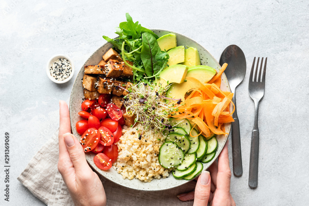 Fototapety, obrazy: Buddha bowl salad in female hands, balanced meal. Bright grey concrete background, table top view. Weight loss, dieting concept