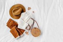 White Knitted Woolen Sweater And Bamboo Bag With Brown Trousers And Hat On White Bed. Women's Stylish Autumn Or Winter Outfit. Trendy Clothes Collage. Flat Lay, Top View.