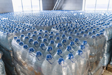 Many Plastic Bottles With Drinking Pure Water And Blue Caps. Goods In Factory Warehouse Or Storehouse Ready For Delivery To Supermarkets