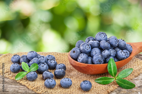 Fotografija fresh ripe blueberry with leaf in wooden spoon isolated on table and white background