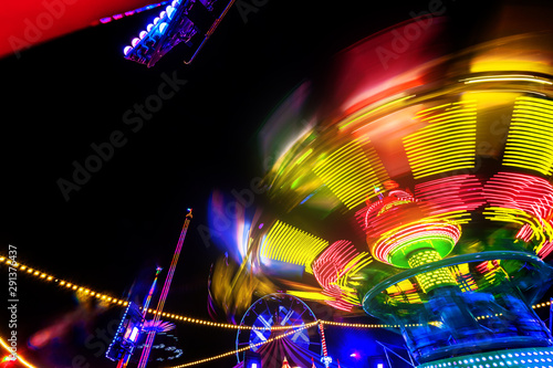 Abstract colorful funfair carosuell in neon colors in motion at a fun fair Fototapet